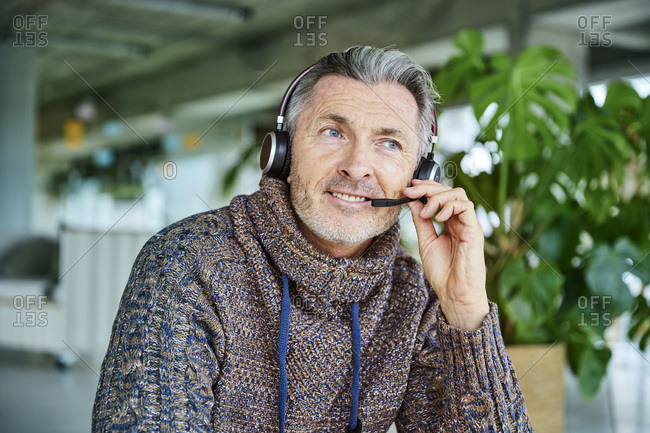 Mature businessman smiling while talking on headset sitting at office