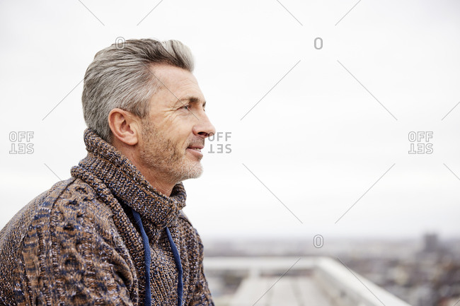 Smiling man wearing sweater looking away while standing at rooftop
