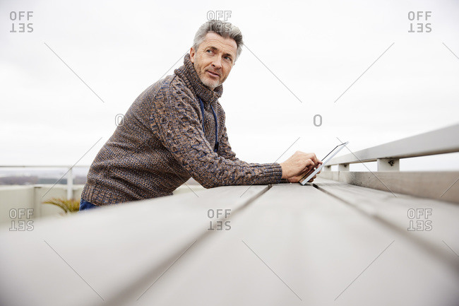 Mature man using digital tablet while standing at rooftop