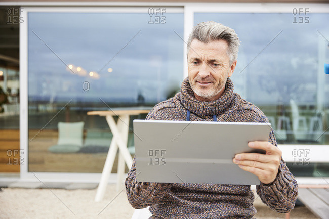 Smiling man using digital tablet while sitting at rooftop