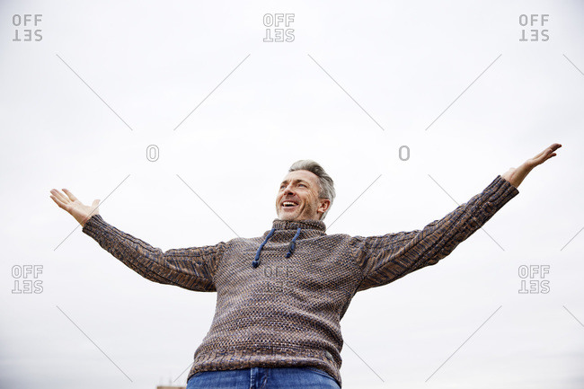 Happy man standing with arms outstretched against sky