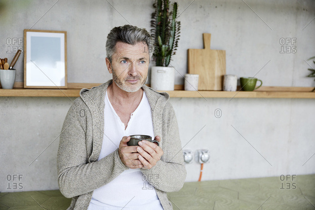Man with coffee cup looking away while sitting at home