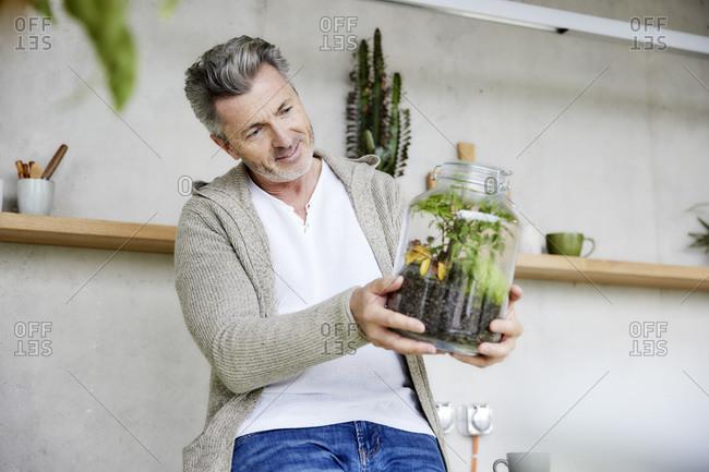 Smiling man holding terrarium while sitting at home