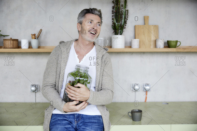 Mature man smiling while holding terrarium sitting at home