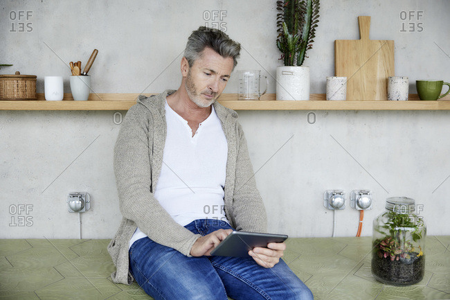 Mature man using digital tablet while sitting at home