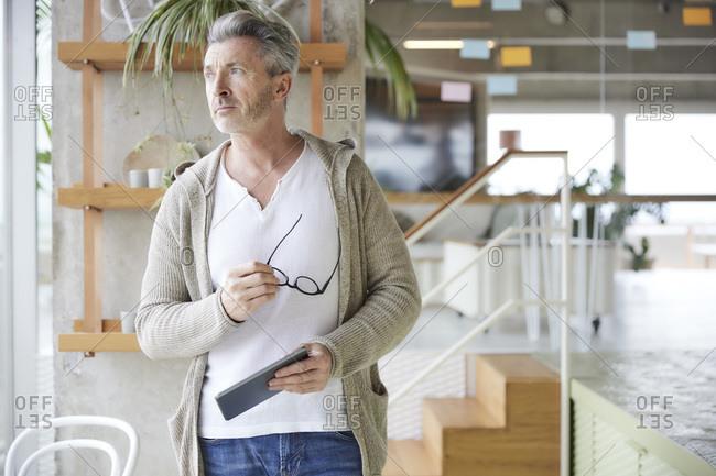 Man with eyeglasses and digital tablet looking away