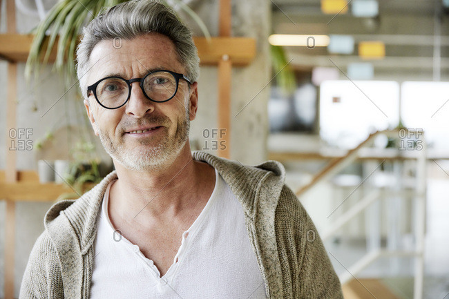 Smiling man wearing eyeglasses looking in a direction