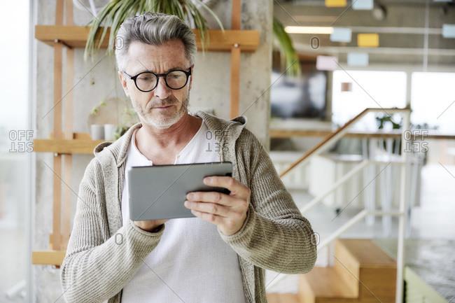 Mature man wearing eyeglasses using digital tablet