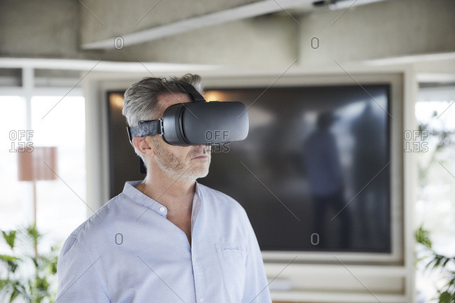 Mature businessman using virtual reality headset while standing at home