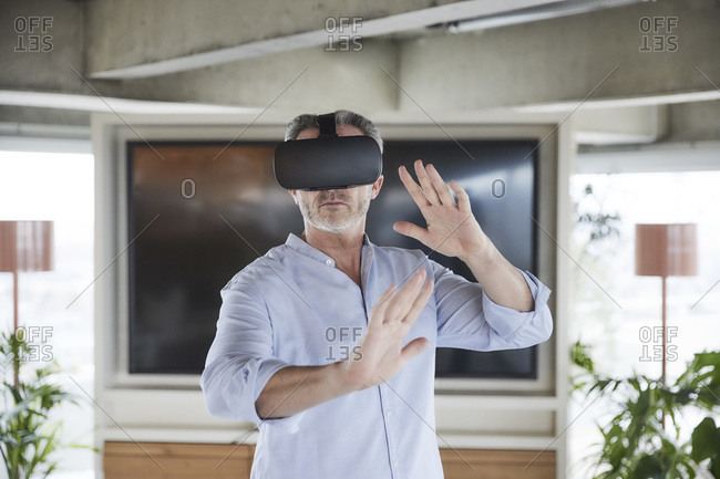 Businessman wearing virtual reality headset standing at home