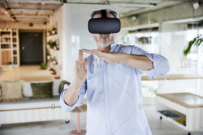 Male businessman wearing virtual reality headset gesturing while standing at home