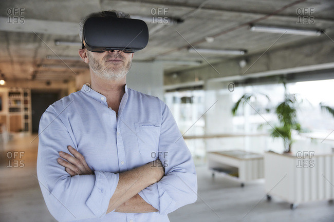 Mature businessman using virtual reality headset while standing with arms crossed at home