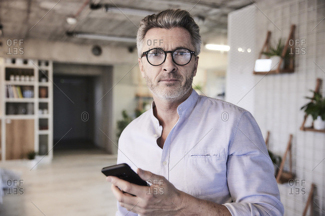 Businessman holding mobile phone looking smart