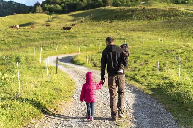 Father walking with two children on walkway of Col des Aravis- Haute-Savoie on sunny day- France