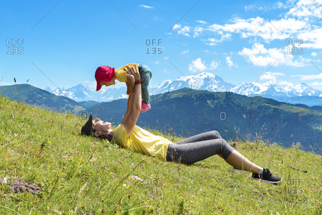 Mother picking up baby girl while lying on grass at Col des Aravis- Haute-Savoie- France