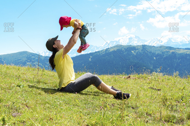 Playful mother with her child playing over grass at Col des Aravis- Haute-Savoie- France