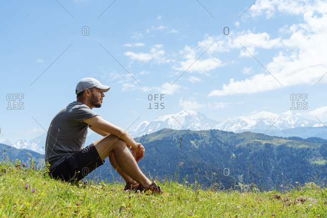 Mid adult man contemplating while sitting over grass at Col des Aravis- Haute-Savoie- France