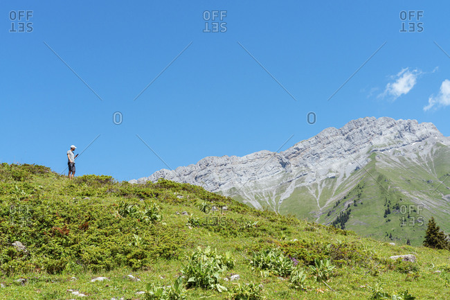 Mid adult man using mobile phone while standing over grass at Col des Aravis mountain- Haute-Savoie against sky- France