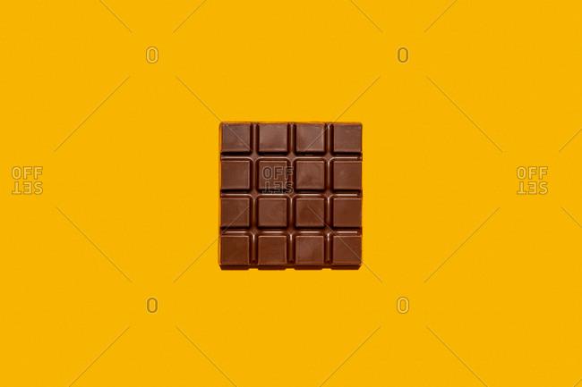 Studio shot of milk chocolate bar against yellow background