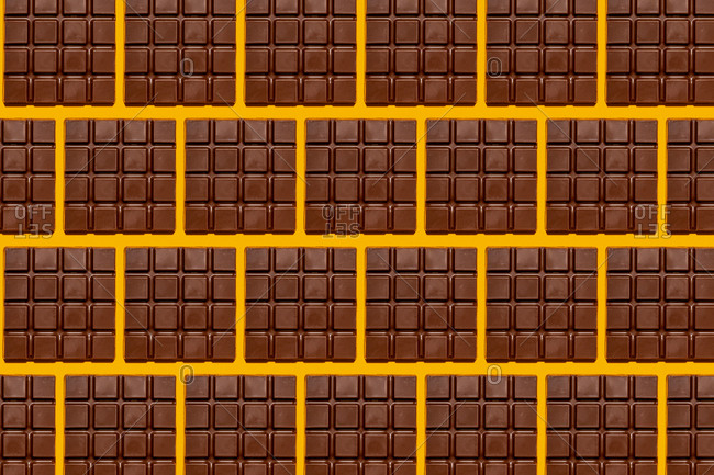 Pattern of chocolate bars against yellow background