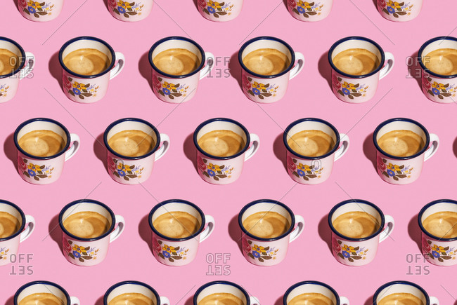Pattern of mugs of coffee against pink background
