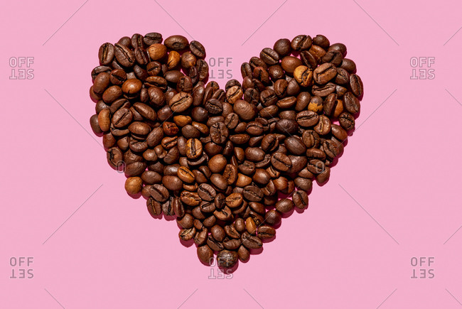 Roasted coffee beans arranged into shape of heart