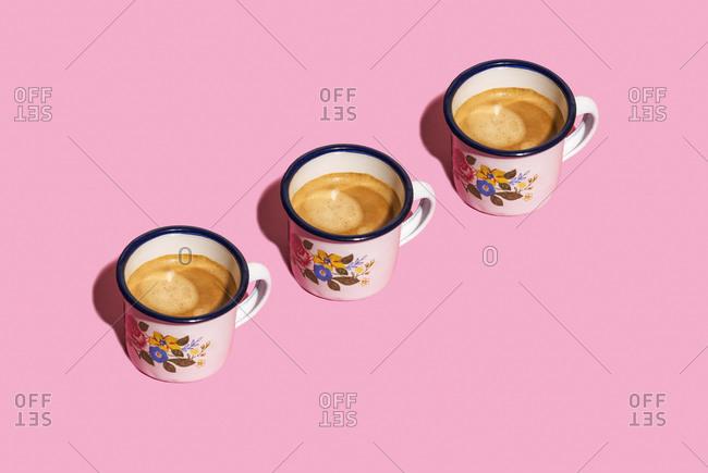 Three old-fashioned metal mugs of coffee