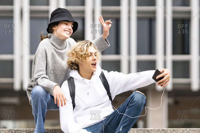 Blond man taking selfie while female friend doing peace sign