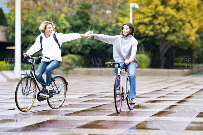 Carefree friends cycling on footpath in park