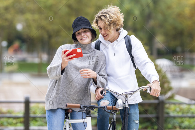 Smiling woman taking selfie standing by male friend with bicycle in park