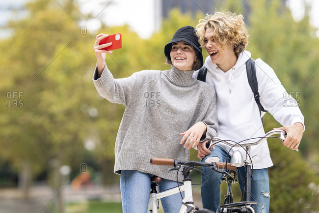 Happy woman taking selfie standing by male friend with bicycle in park