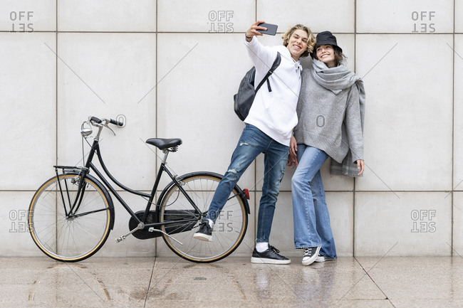 Man taking selfie standing by female friend with bicycle against wall on footpath
