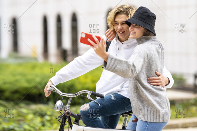Woman with arm around of male friend talking selfie on smart phone in park