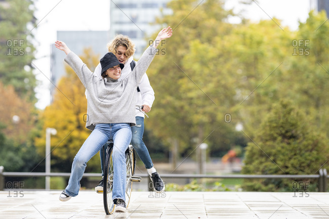Carefree woman sitting with male friend on bicycle in park