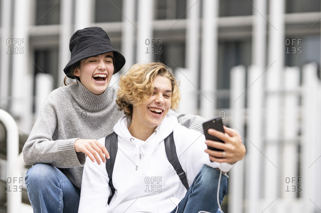 Young friends laughing while taking selfie on mobile phone
