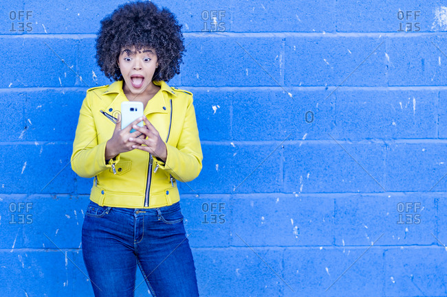 Afro woman with shocked reaction using mobile phone against blue wall