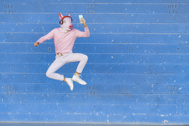 Young man with pig mask jumping while taking selfie and listening music against blue wall