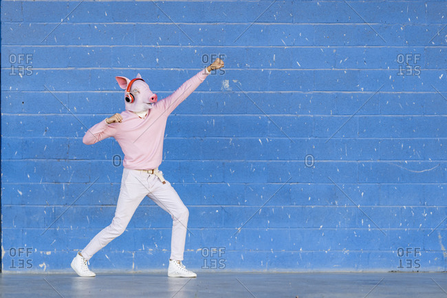 Fashionable young man wearing pig mask pretending to fly against blue wall
