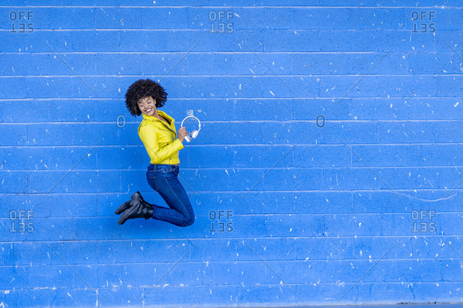Cheerful young woman holding headphones while jumping against blue wall