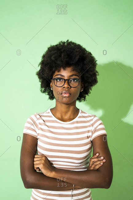 Young woman wearing eyeglasses standing with arms crossed against green background