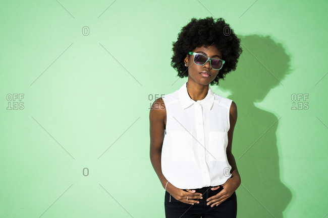 Young woman wearing sunglasses standing against green background
