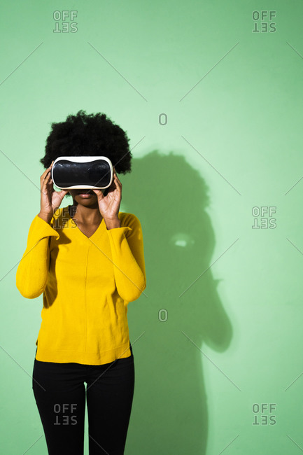 Young woman using virtual reality headset while standing against green background