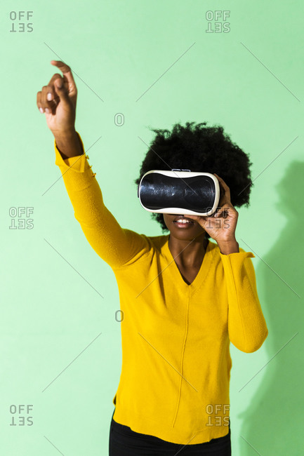 Young woman using virtual reality simulator standing with hand raised against green background