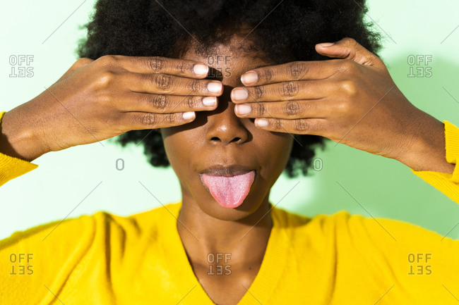 Woman sticking out tongue while covering eyes with hand standing against green background