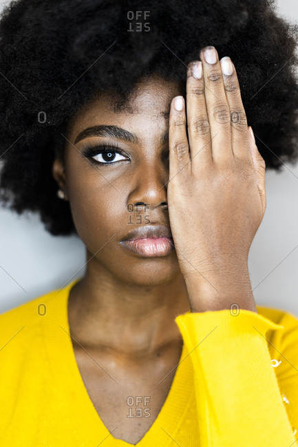 Young woman covering eye with hand while staring against white background