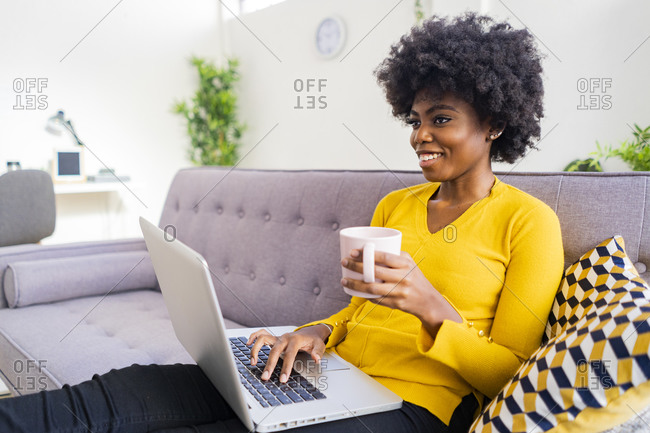Smiling woman with coffee cup using laptop while sitting on sofa at home