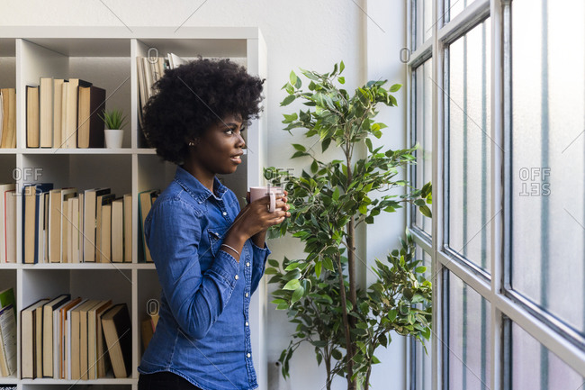 Young curly hair woman with coffee cup looking through window while standing at home