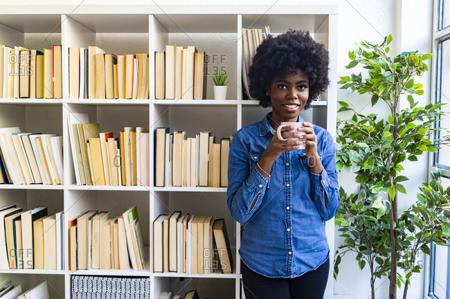 Smiling young woman drinking coffee while standing against bookshelf at home