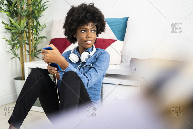 Curly hair woman with mobile phone and headphones looking away while sitting at home