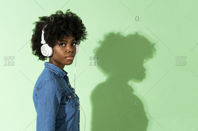 Young woman wearing headphones listening music while standing against green background